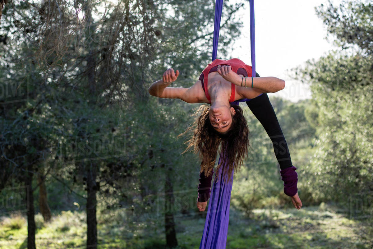 Young girl acrobat. Practicing aerial silks. Woman doing circus stunts with clothes in the forest. Candy cane trick pose. Royalty-free stock photo