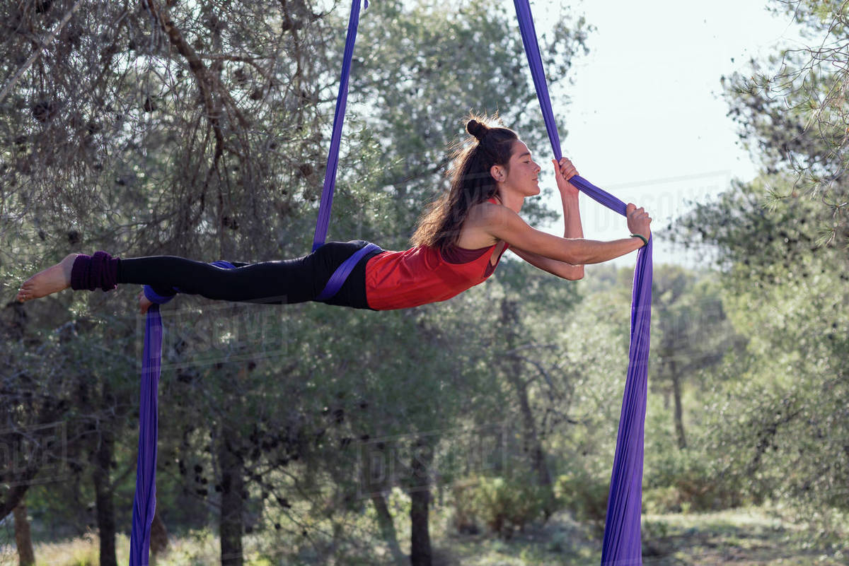 Young girl acrobat. Practicing aerial silks. Woman doing stunts with clothes in the forest. Horizontal position. Royalty-free stock photo