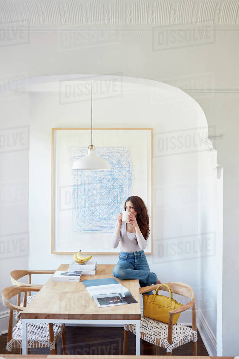 Woman drinking coffee on kitchen table in nook Royalty-free stock photo