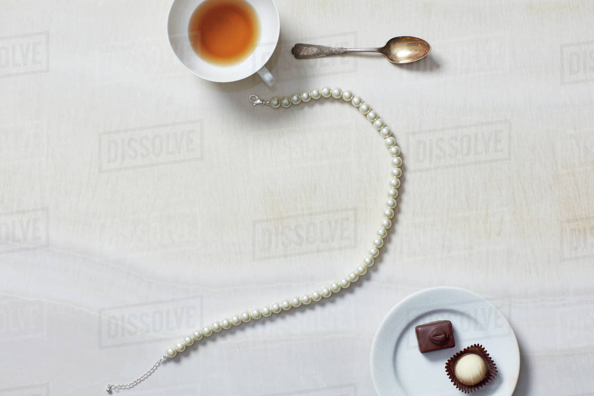 Still life of necklace, tea cup, chocolates Royalty-free stock photo