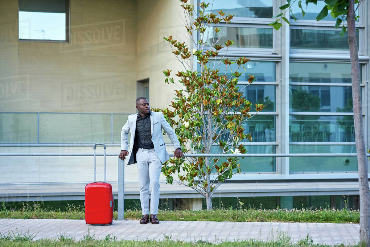 African-American in a white suit and a red suitcase. Royalty-free stock photo