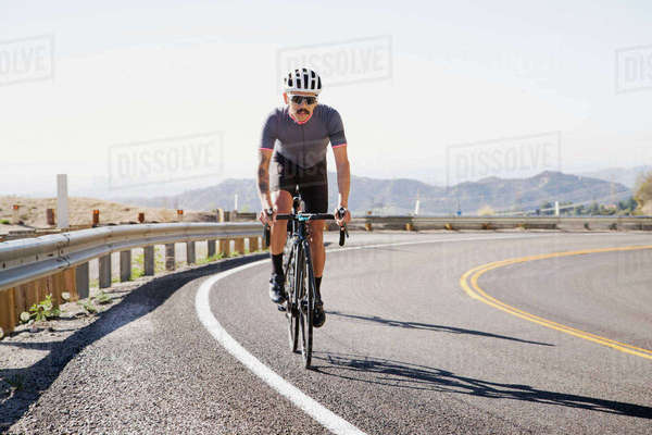 Man cycling on road against clear sky Royalty-free stock photo