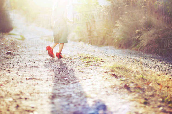 Rear view of girl walking on footpath during sunny day Royalty-free stock photo
