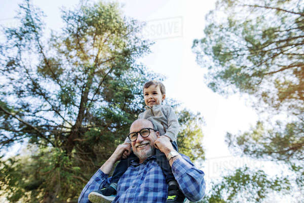 Low angle view of happy senior man carrying grandson on shoulders against sky Royalty-free stock photo