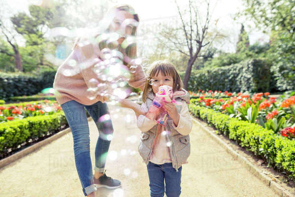 Mother and daughter playing with bubble gun in park Royalty-free stock photo