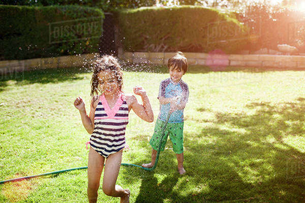 Brother and sister (4-5, 6-7) playing with hose in backyard Royalty-free stock photo