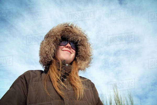 Woman In Hooded Jacket Smiling Against Blue Sky Royalty-free stock photo