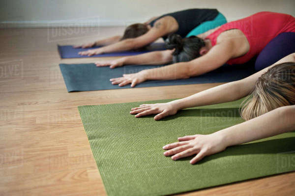 Females performing yoga in child's pose at health club Royalty-free stock photo