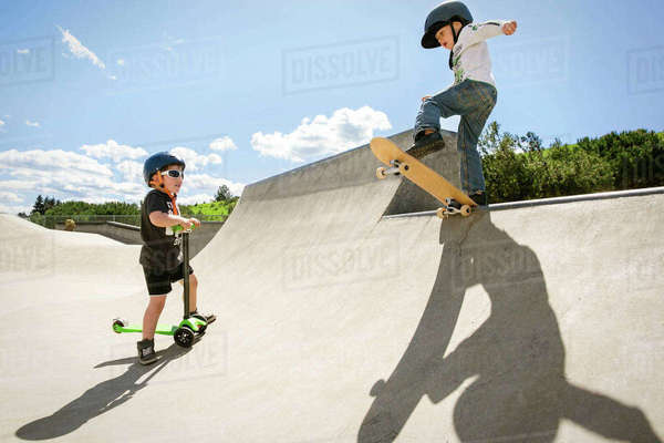 Boy looking at friend performing stunt on skateboard ramp Royalty-free stock photo