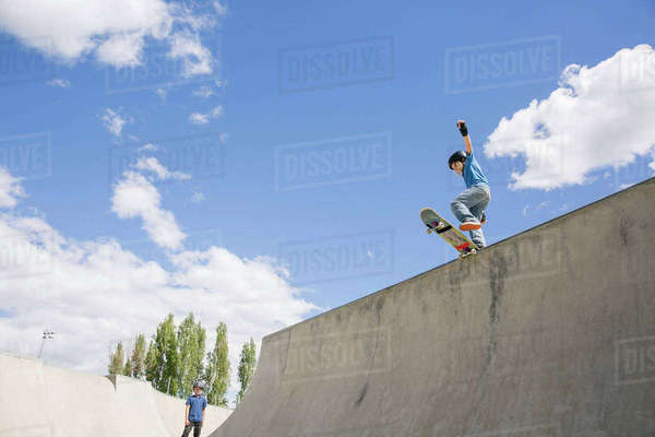 Low angle view of boy skateboarding on ramp against blue sky Royalty-free stock photo