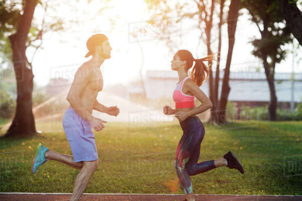 Side view of couple exercising at park on sunny day Royalty-free stock photo