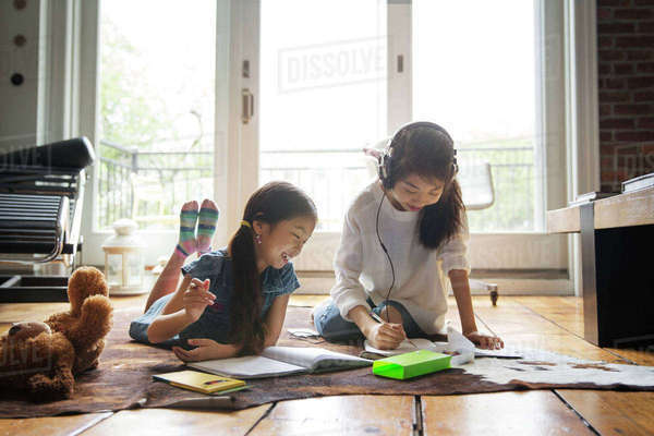 Happy sisters studying on carpet at home Royalty-free stock photo