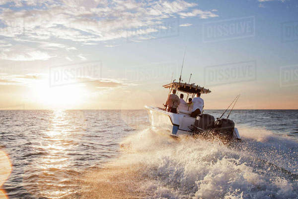 Men enjoying in speedboat at sea against sky during sunset Royalty-free stock photo