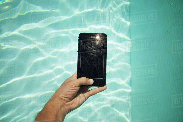 Cropped image of hand holding smart phone over swimming pool Royalty-free stock photo