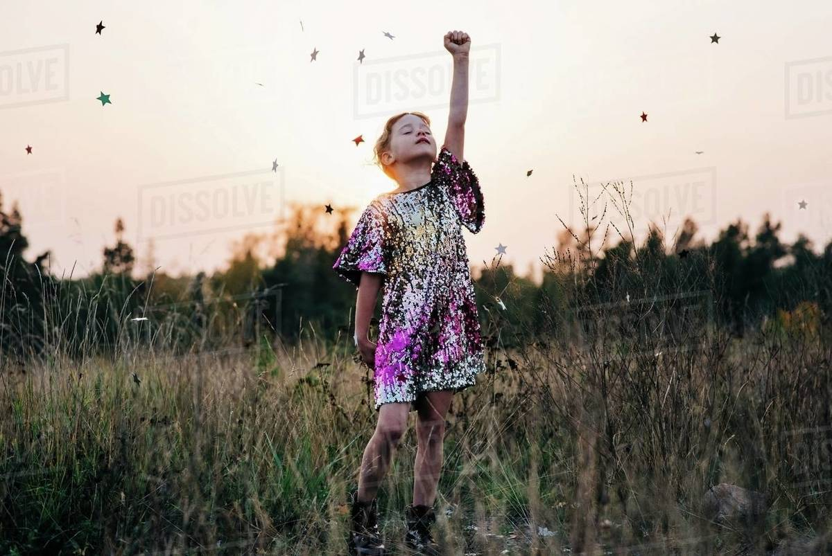 Girl standing strong in a sparkly dress with star confetti falling Royalty-free stock photo