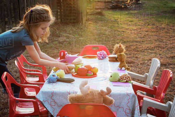 Side view of girl serving sandwich on table at yard Royalty-free stock photo