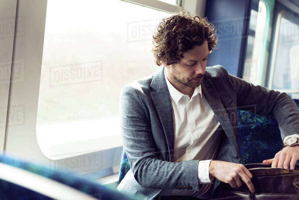 Businessman searching in bag while sitting in train Royalty-free stock photo
