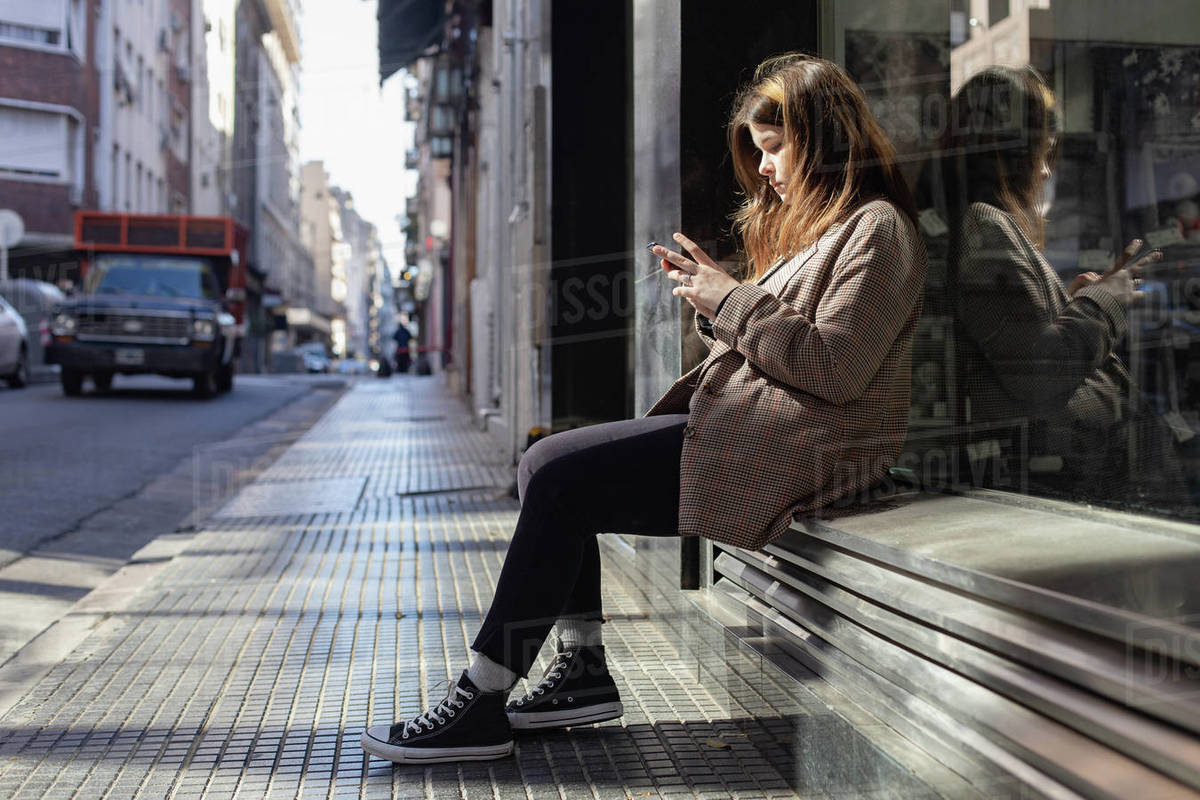 Teenage girl with a smartphone on a street in Buenos Aires Royalty-free stock photo