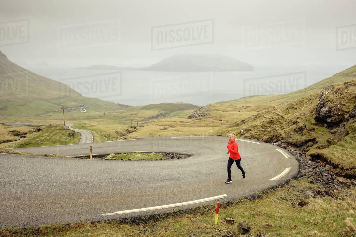 Sportswoman running on winding road Royalty-free stock photo