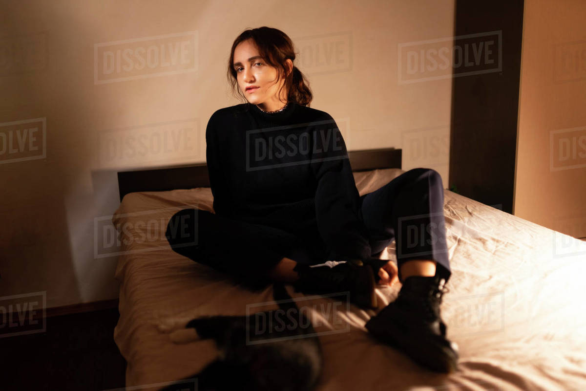 Woman sitting on bed in shoes Royalty-free stock photo