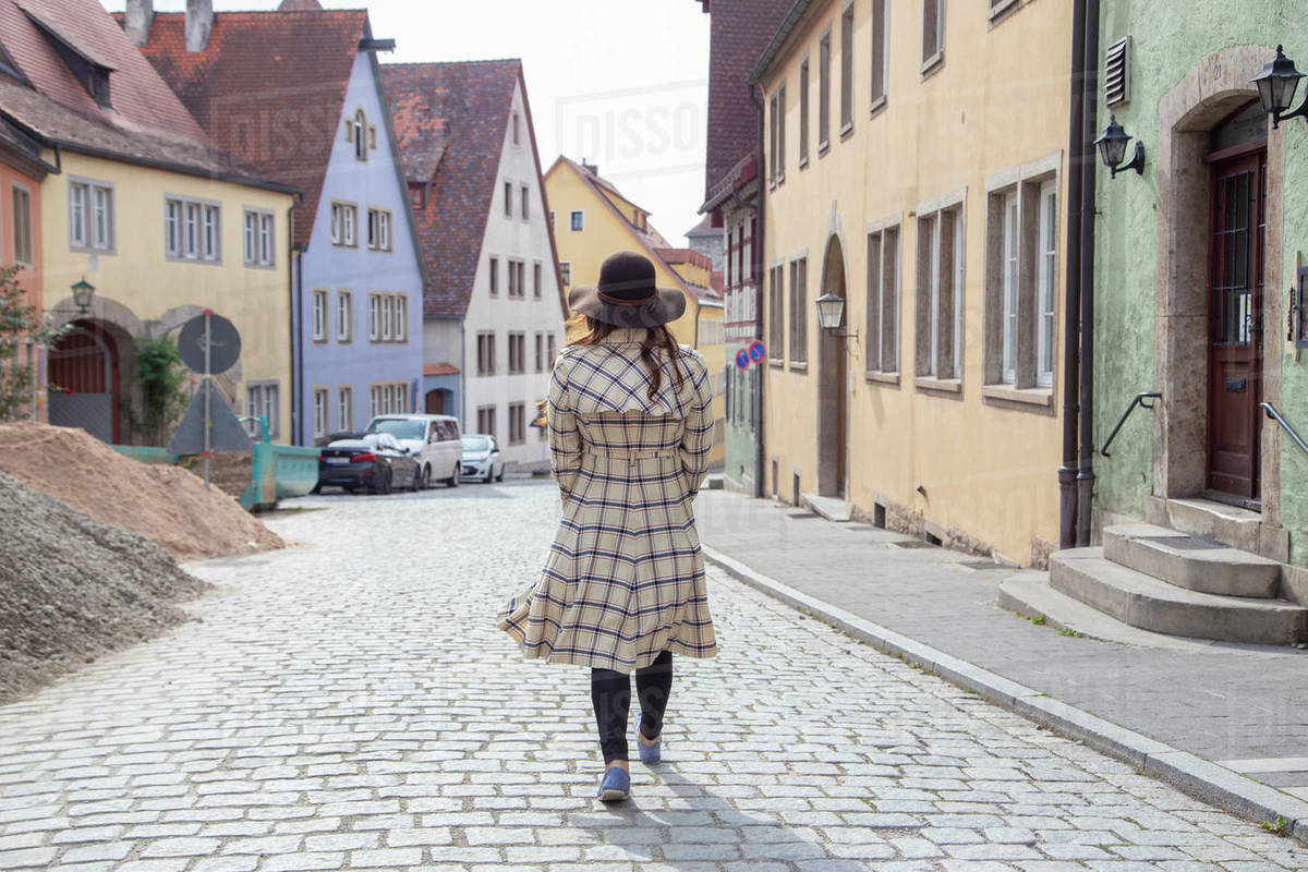 A woman in a long coat wandering the streets of Germany Royalty-free stock photo
