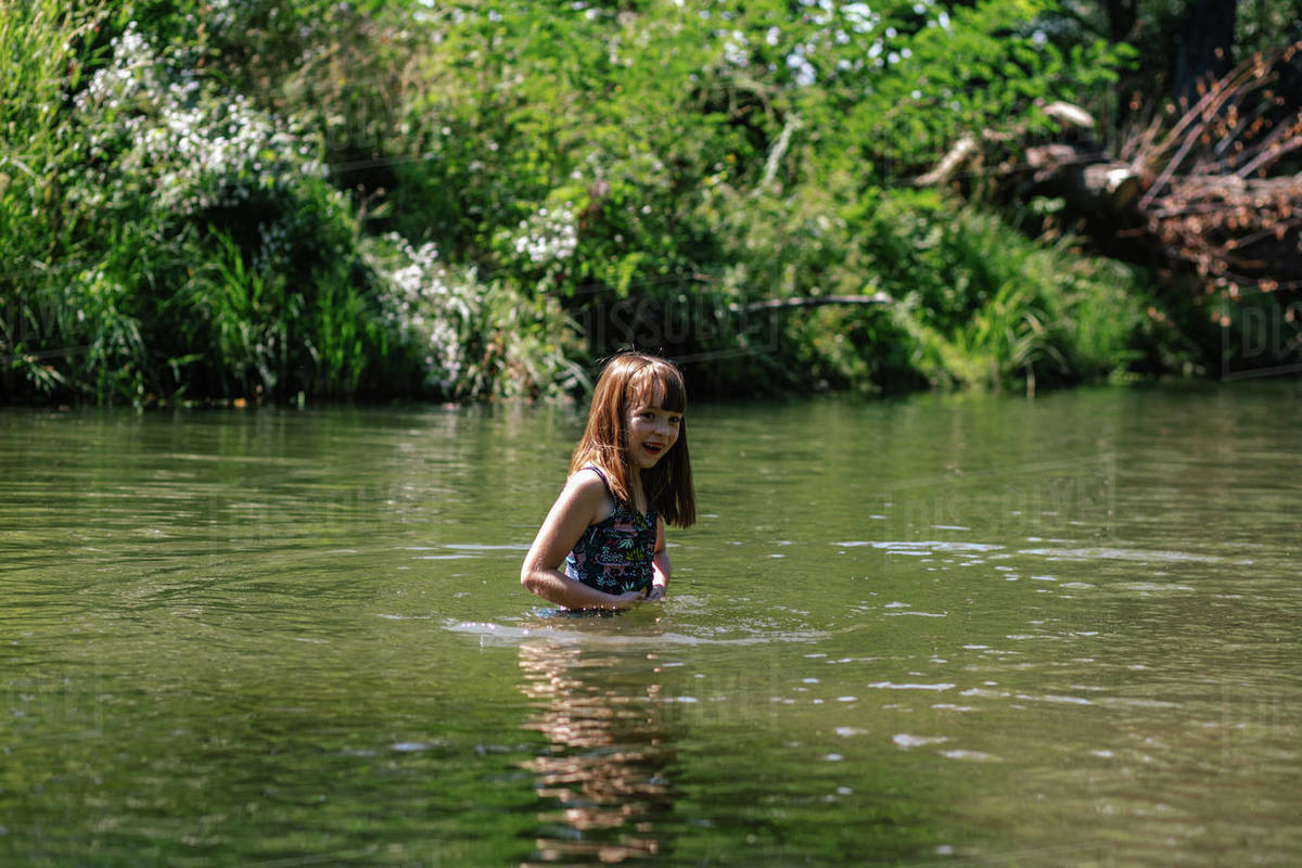 Happy young girl swimming in a deep creek on a summer day Royalty-free stock photo