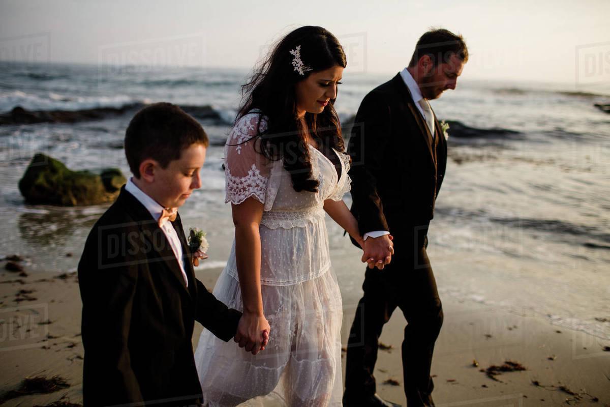 Newlyweds & Nine Year Old Son Walking Along Beach in San Diego Royalty-free stock photo