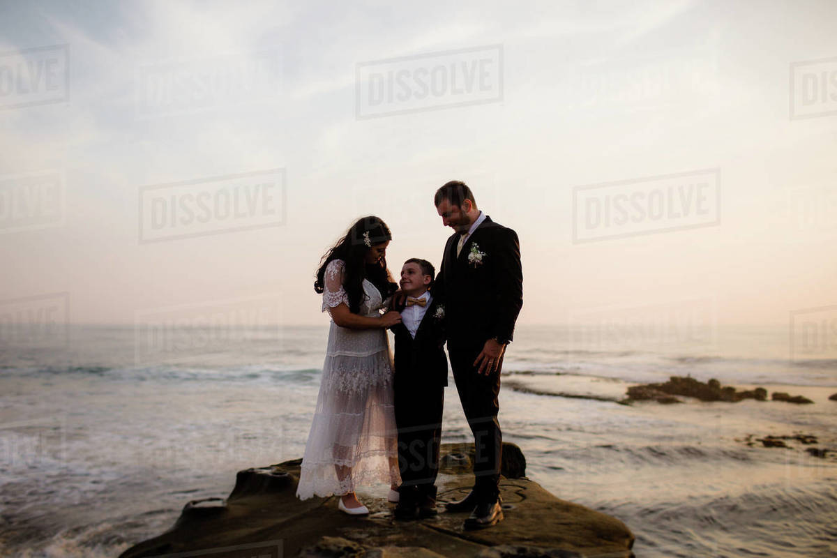 Newlyweds & Nine Year Old Son Standing on Rock at Beach in San Diego Royalty-free stock photo