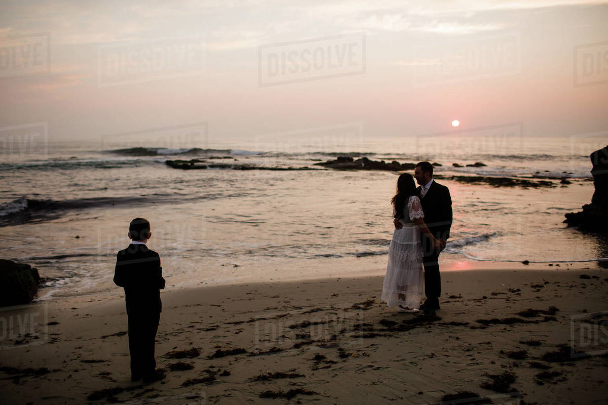 Newlyweds & Nine Year Old Son Posing on Beach at Sunset in San Diego Royalty-free stock photo