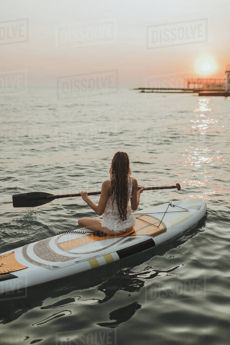 Young surfer girl sitting on a Board with a paddle sunset Royalty-free stock photo