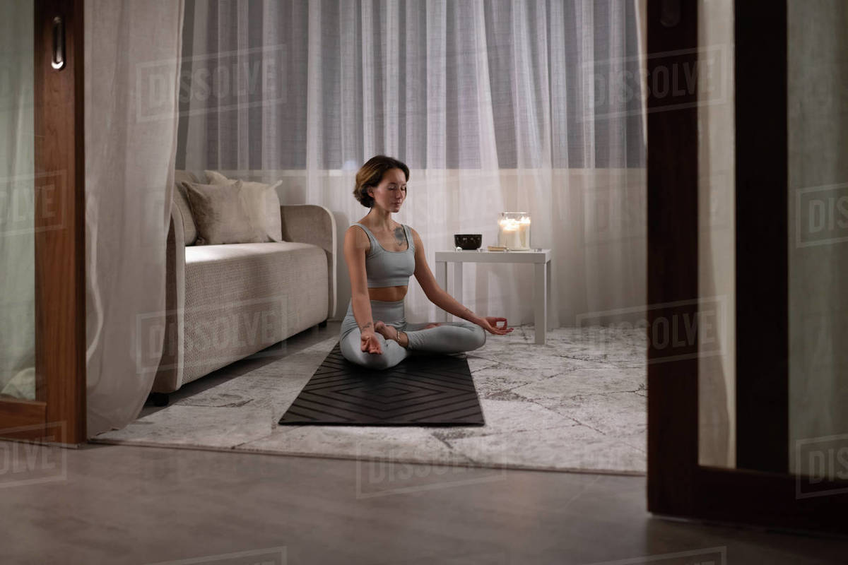 Young woman meditating in living room Royalty-free stock photo