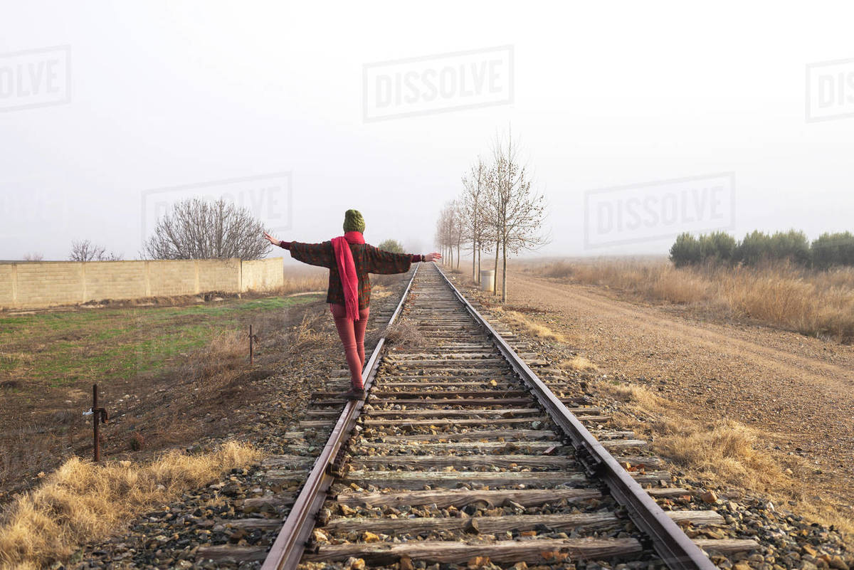 Rear view of a girl balancing on train rail while walking Royalty-free stock photo