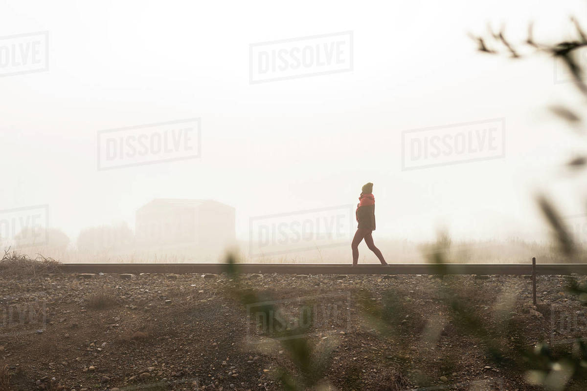 Thoughtful woman walking on a foggy railroad while looking away Royalty-free stock photo