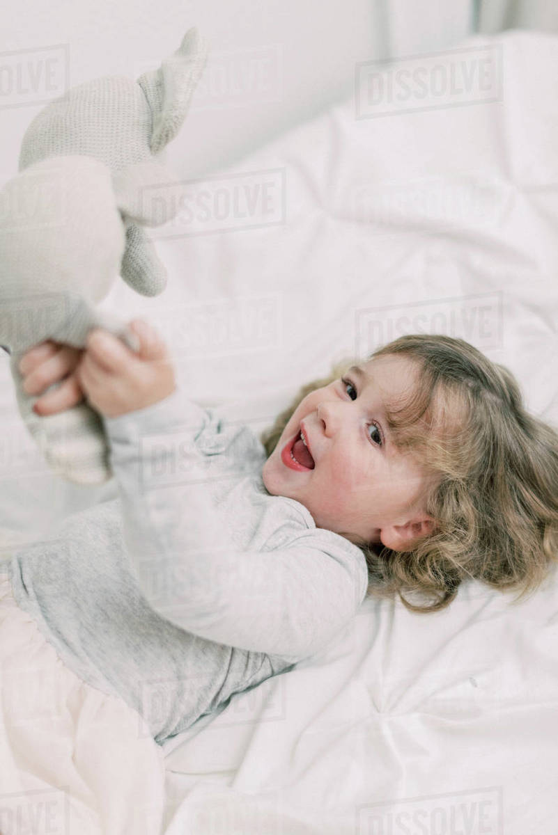 Little toddler playing with her stuffed animal on a bed Royalty-free stock photo