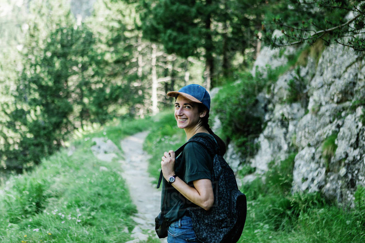 Smiling female hiker walking on a mountain trail Royalty-free stock photo