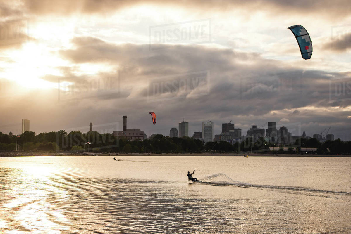 A woman kiteboarding on a summer evening with a dark Boston skyline Royalty-free stock photo