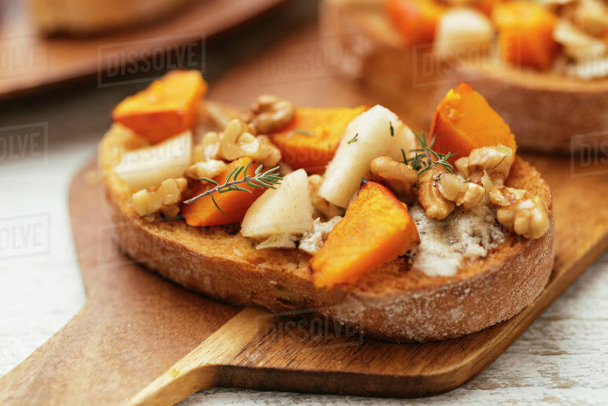 Fall Bruschetta with Squash, Pear, Vegan Feta and Maple Walnut Drizzle Royalty-free stock photo