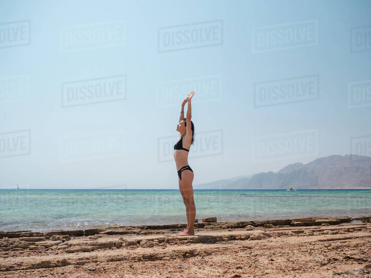 Young brunette woman doing exercises on the beach near sea Royalty-free stock photo