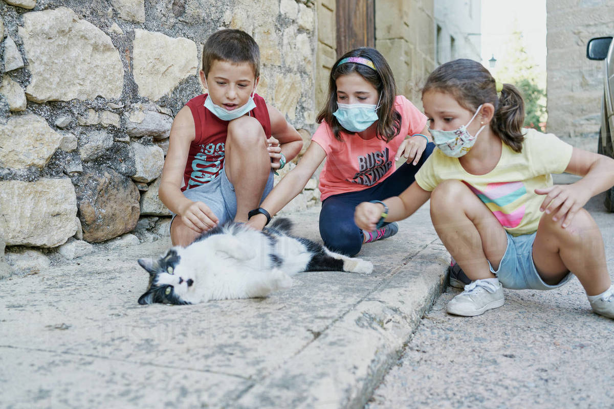 Three children with masks for the covid19 play with a black and white cat that is lying in the street Royalty-free stock photo
