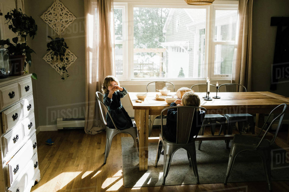 Two kids eating soup and bread for lunch together at the table Royalty-free stock photo