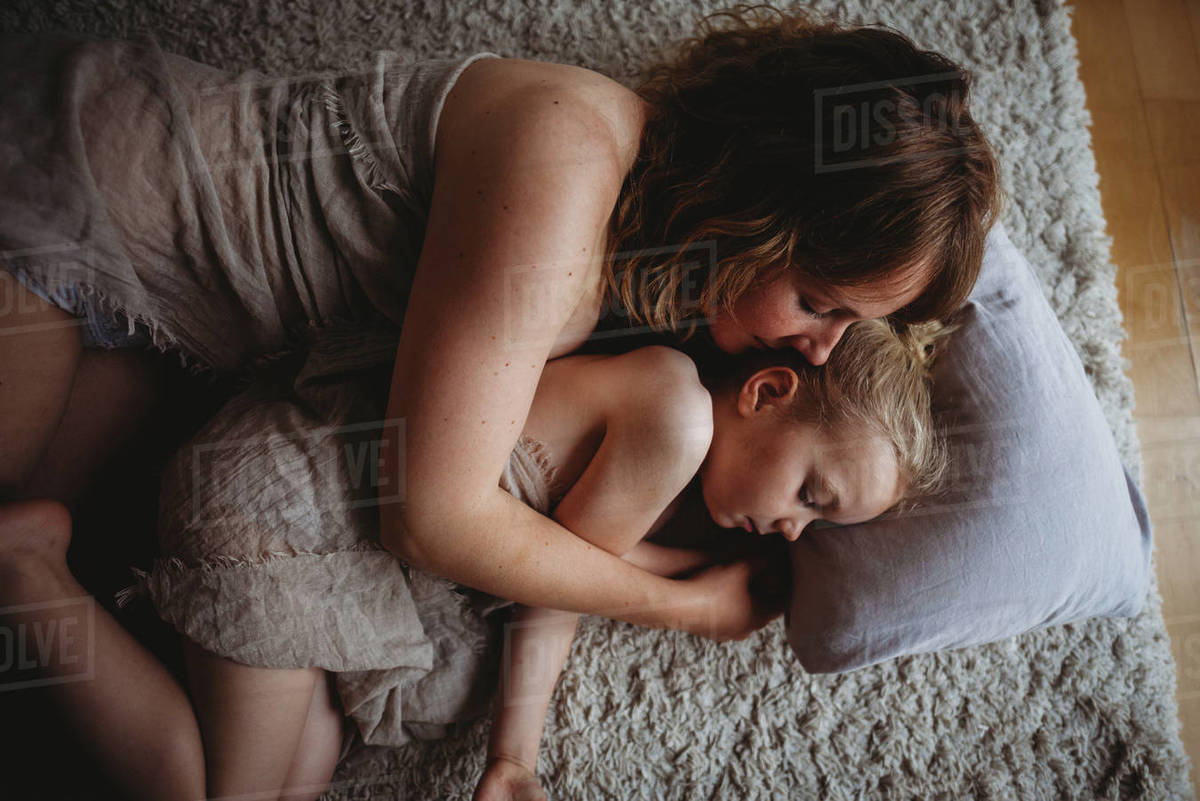 Mother and daughter hugging sleeping on the ground in bedroom Royalty-free stock photo