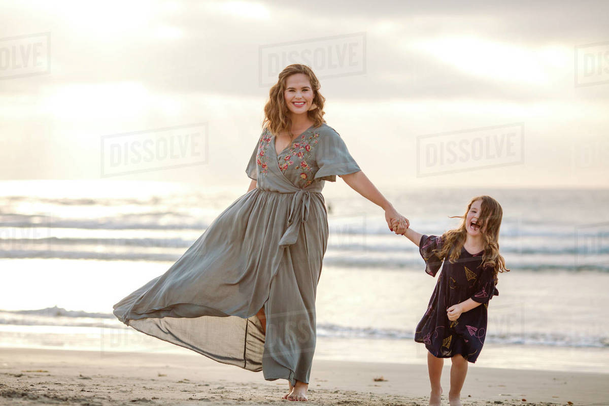 Beautiful mom in flowing dress walking on beach with 3 yr old daughter Royalty-free stock photo