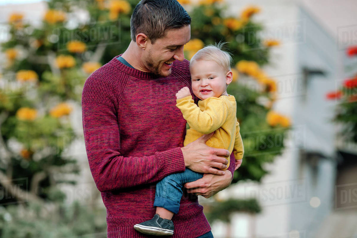 Laughing young dad holding happy blonde baby in yellow shirt Royalty-free stock photo