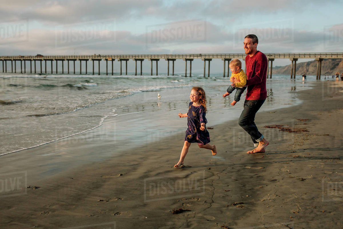 Laughing dad holding baby chases daughter on beach near pier Royalty-free stock photo