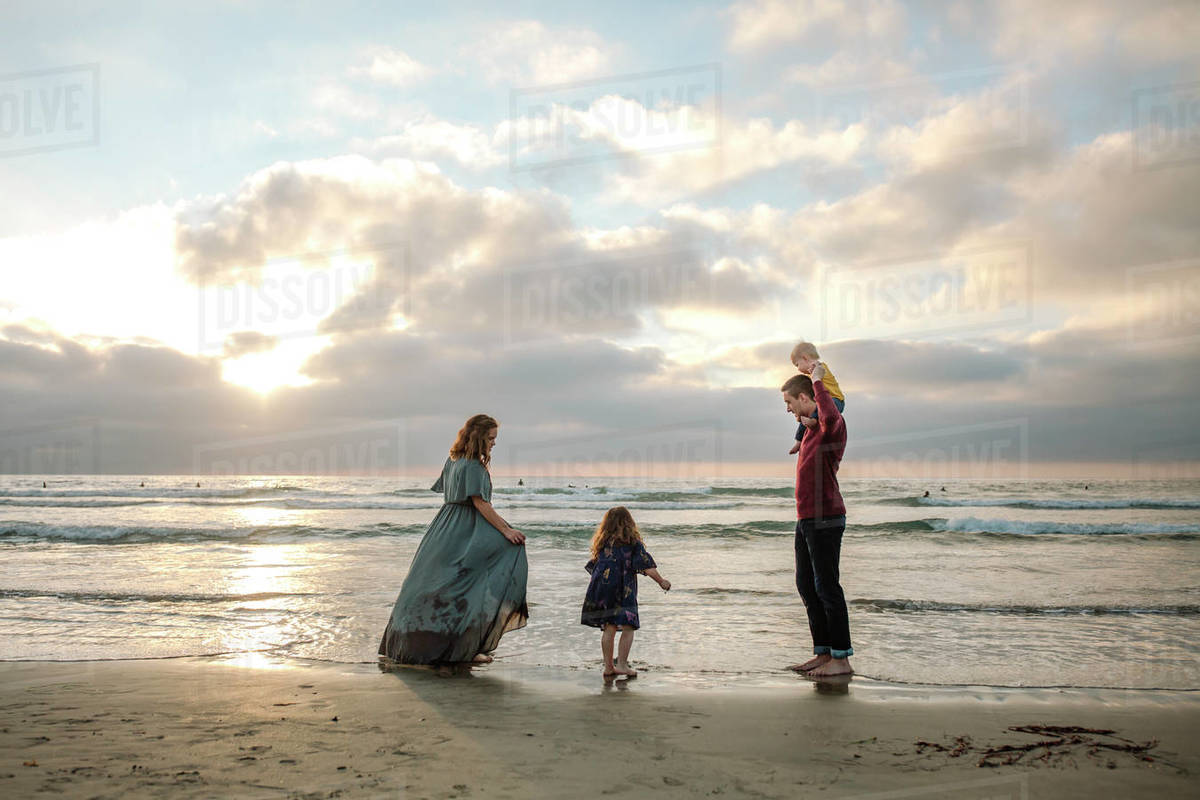 Mom in long dress at beach with husband, daughter and baby at sunset Royalty-free stock photo