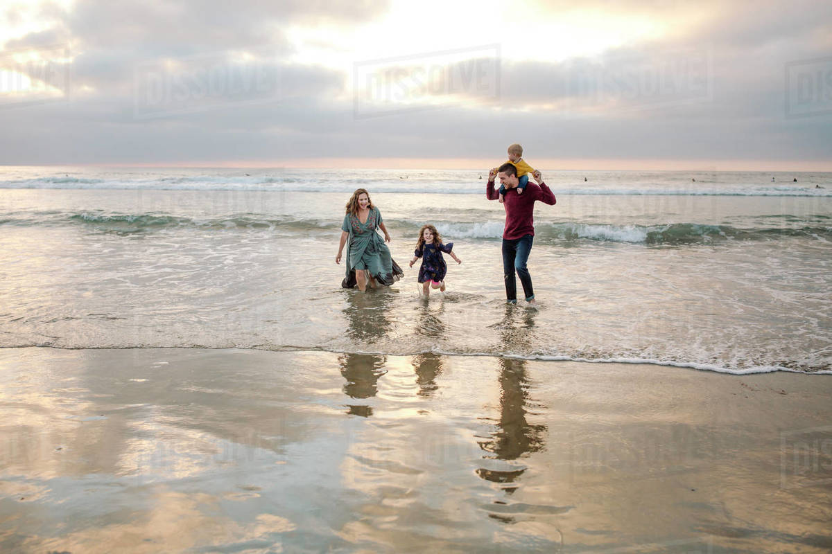 Young family wearing street clothes wading in ocean surf at sunset Royalty-free stock photo