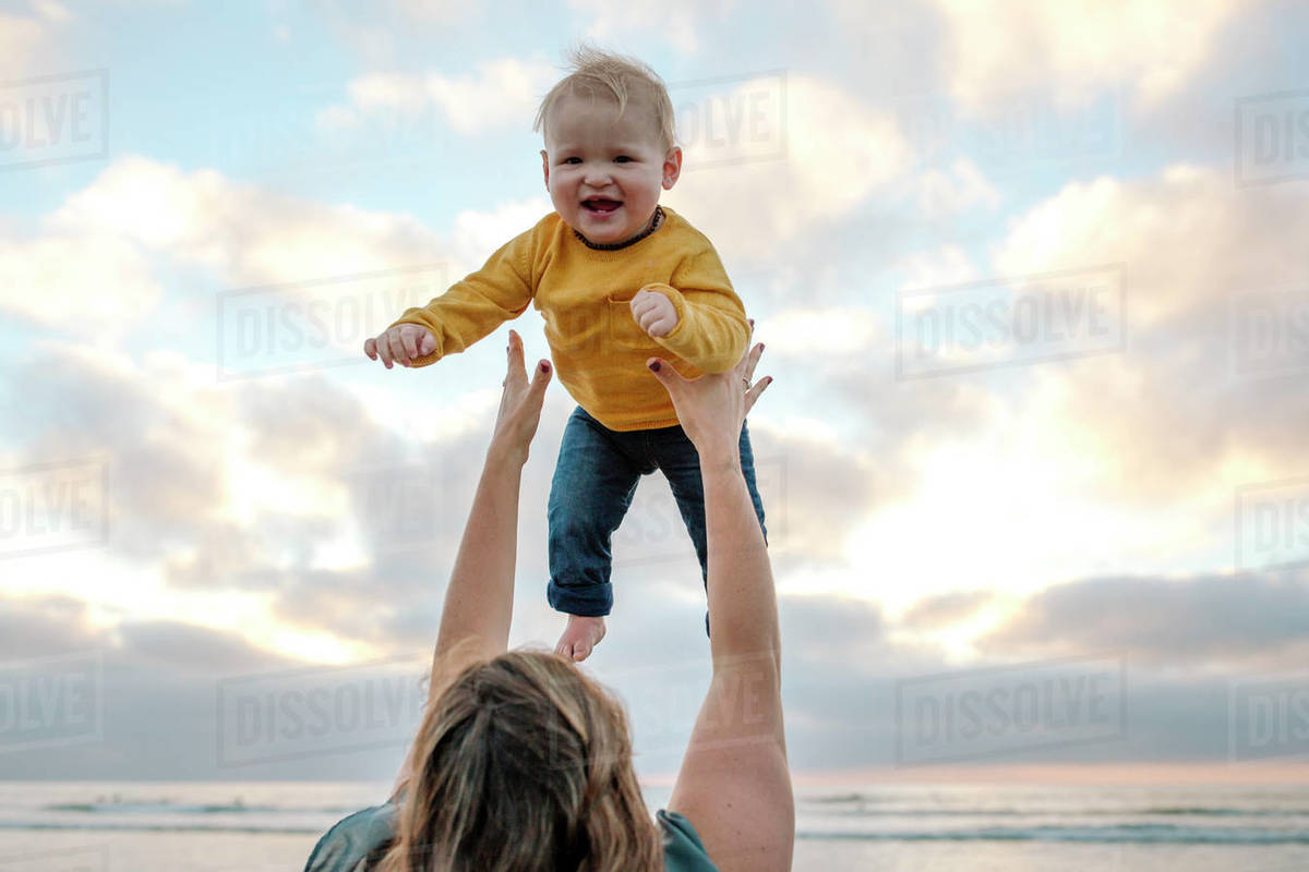 Mom tossing happy baby high into air with ocean sunset as backdrop Royalty-free stock photo