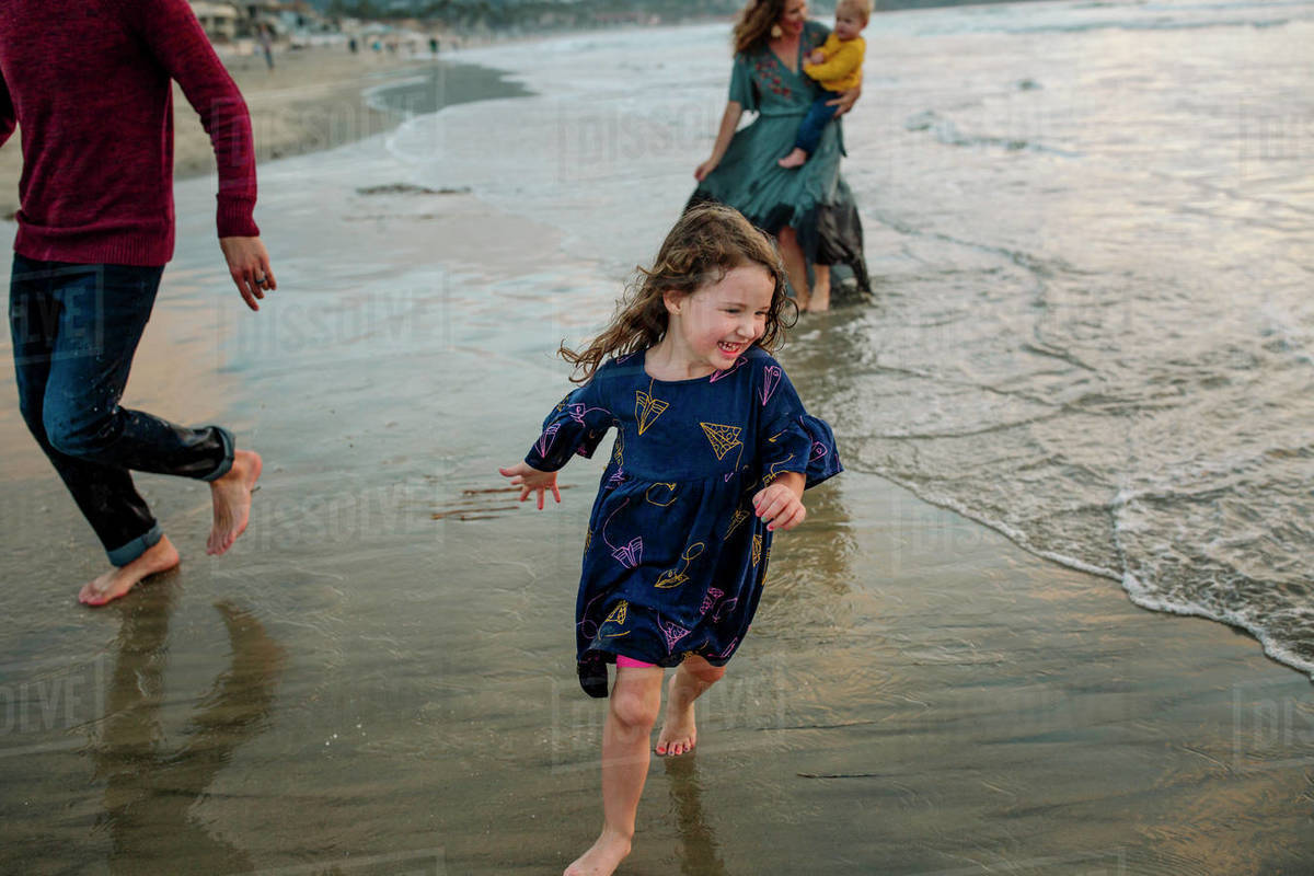 Laughing girl and family running through ocean surf in street clothes Royalty-free stock photo