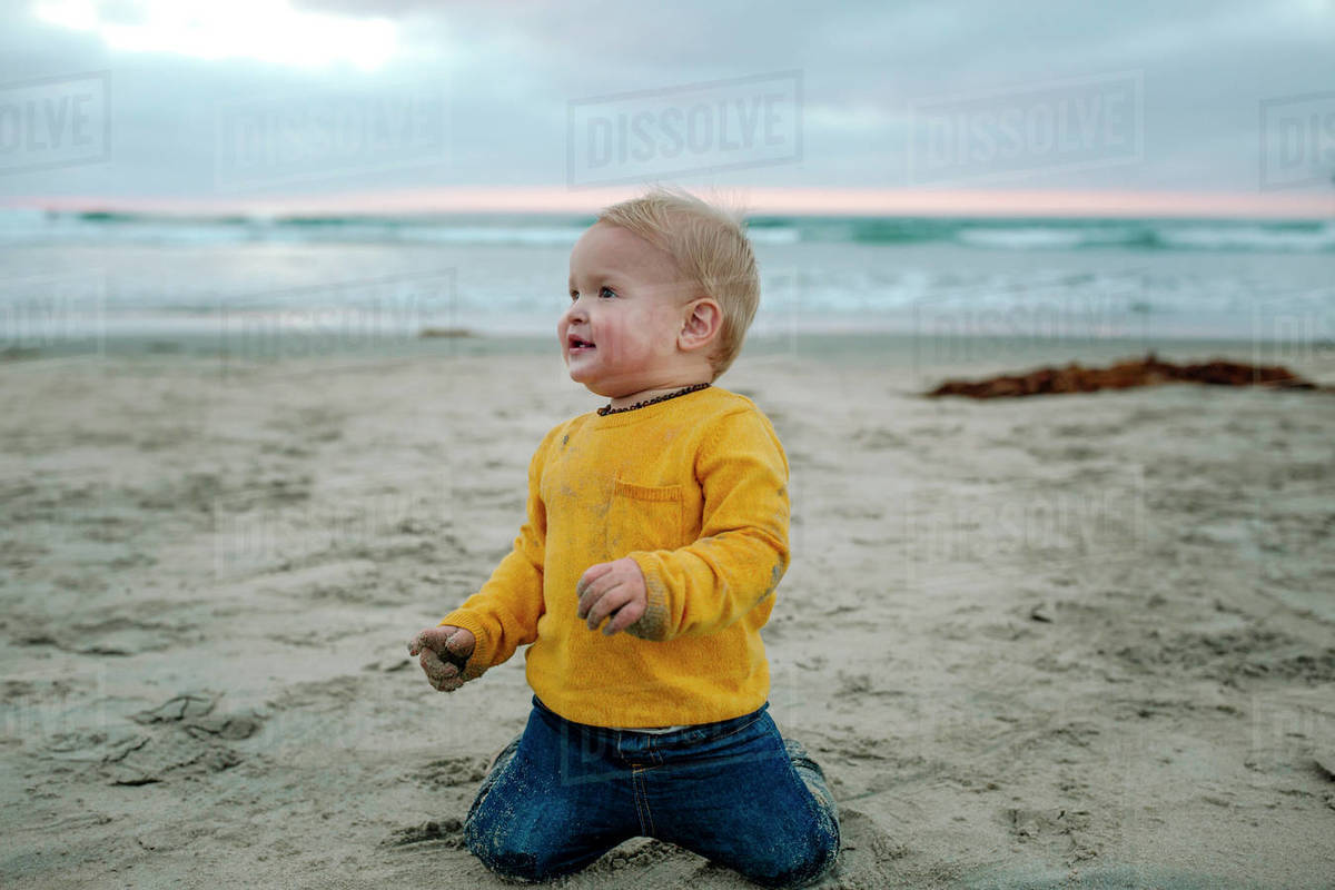 Young smiling child in yellow shirt playing in sand at the ocean Royalty-free stock photo