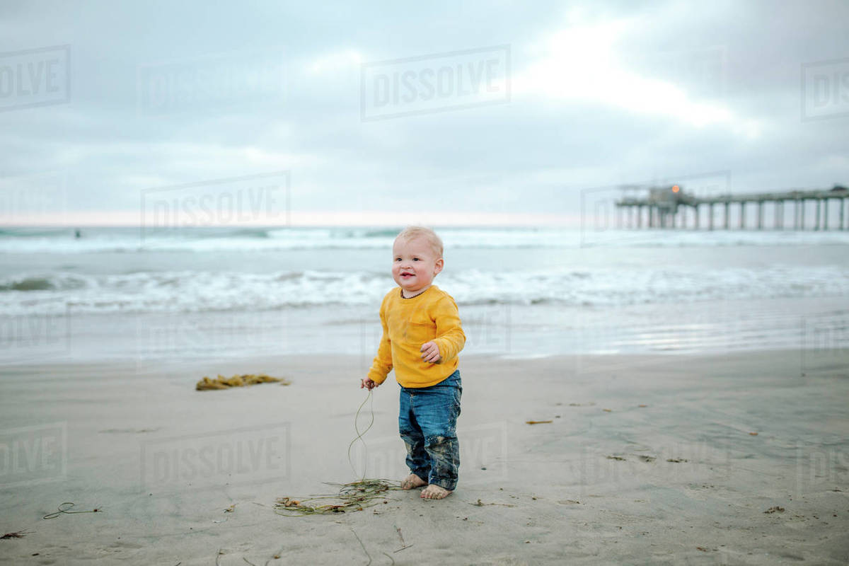 Happy toddler in wet clothes playing on beach near pier Royalty-free stock photo